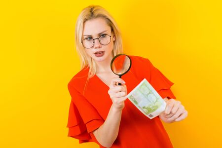 Portrait of attractive blonde woman in red dress and eyeglasses isolated on yellow background looking through magnifying glass on euro banknote checking if it is fake counterfeiter concept.
