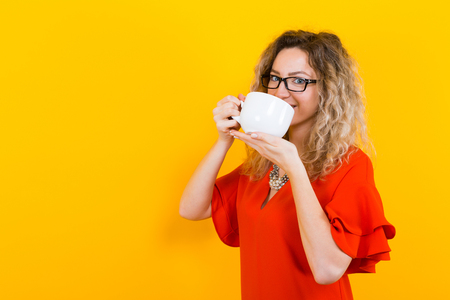 Portrait of attractive curly-haired woman in glasses and red dress isolated on orange background with copyspace drinking from white mug perfect for putting any design on.