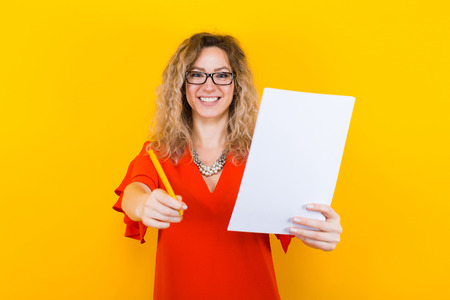 Portrait of attractive curly-haired businesswoman in red dress and eyeglasses isolated on orange backgroung holding blank paper list and pencil signing a contract agreement bargain concept.