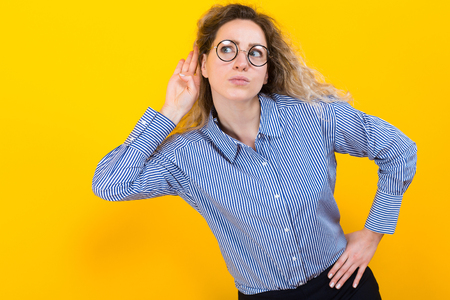 Portrait of curly-haired woman in striped shirt isolated on orange background trying hard to secretly listen to conversation hand to ear interested at gossip she hears privacy violation concept.
