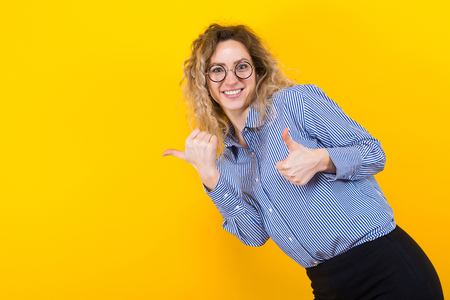 Portrait of curly-haired nerdy woman in striped shirt isolated on orange background with copyspace showing her thumbs up. Stock Photo