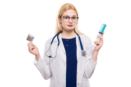 Female doctor in white coat wears stethoscope and glasses holds condom and big syringe isolated on white background with copyspace safety sex pregnancy sexually transmitted diseases prevention concept.