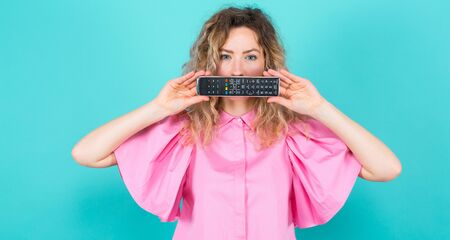 Portrait of attractive bored curly-haired woman in pink blouse isolated on blue backgroung hiding her mouth behind remote control turning TV over concept.