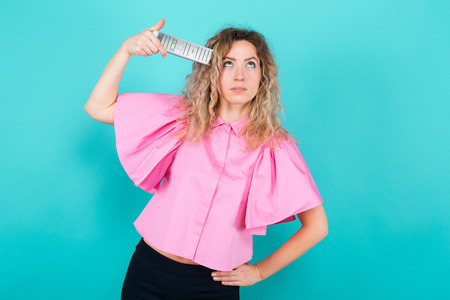 Portrait of attractive bored curly-haired woman in pink blouse isolated on blue backgroung holding remote control near her head as if it is gun boredom concept.