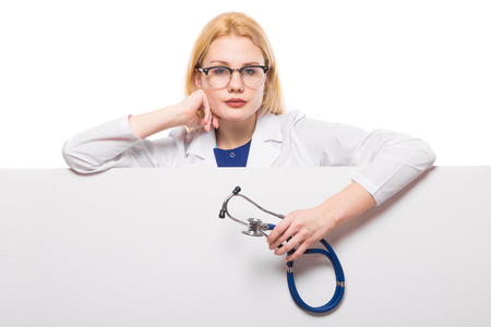 Portrait of female doctor in white coat holding stethoscope propping up her cheek and wearing glasses isolated on white background with copyspace.