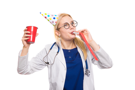 Funny female doctor glasses with stethoscope wears birthday cap and blows in party whistle hold red plastic cup with drink on white background with copyspace corporate medical party concept.