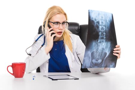 Hesitating female doctor physician in white coat and glasses sit at table studies X-ray consults digital tablet pc and colleague on phone isolated on white background can not make diagnosis concept.