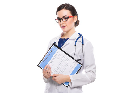 Portrait of young beautiful brunette caucasian female doctor in white coat standing in office and looking in camera confident friendly experienced skilful positive cheerful smiling happy gp dentist.