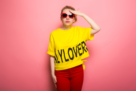 Woman in yellow T-shirt, red jeans and sunglasses covering hwr forehead with her palm isolated on pink background with copyspace.