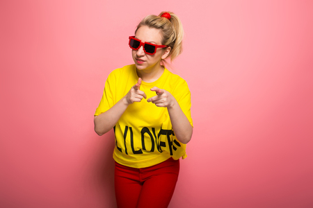 Attractive woman in yellow T-shirt, red jeans and sunglasses pointing with fingers at camera and flirting isolated on pink background with copyspace invitation concept.