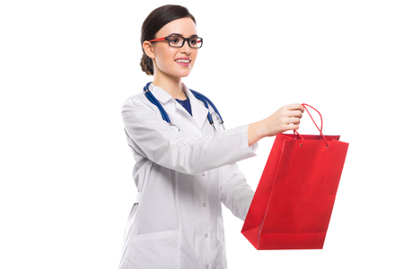 Portrait of young attractive female doctor in white coat smiling looking at client offering shopping bag confident friendly experienced skilful positive cheerful lucky happy brunette caucasian beautiful pretty gp isolated. Stock Photo
