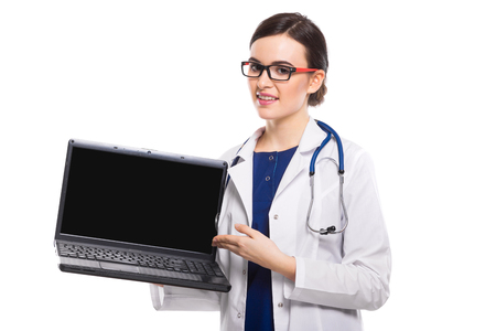 Portrait of young pretty female doctor in white coat standing in office and looking in camera showing on her laptop checking her schedule confident friendly experienced skilful beautiful attractive brunette caucasian gp.