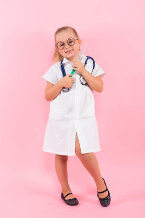Portrait of little girl dressed like doctor in white coat and eyeglasses wearing stethoscope and holding syringe isolated on pink background with copyspace pediatrics concept.