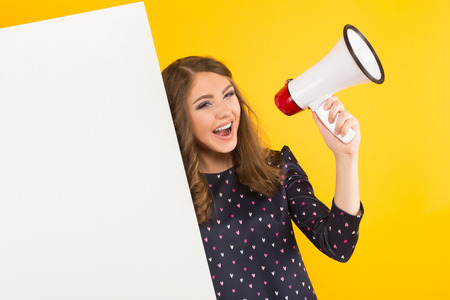 Portrait of attractive happy brunette woman in blouse isolated on yellow background hiding behind emty blank board and speaking into megaphone your text here concept. Stock Photo