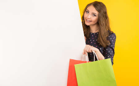 Portrait of attractive happy brunette woman in blouse isolated on yellow background holding colourful shopping paper bags near white empty blank board your text here advertising concept.