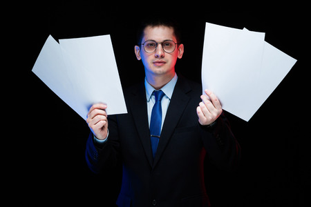 Young business man in black suit standing in office looking in camera with documents in his hands thoughtful handsome confident successful sophisticated classic smart elegant modern serious.