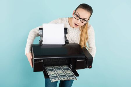 Portrait of attractive happy woman in sweater and eyeglasses isolated on blue background holding printer printing dollar banknotes counterfeiter greed concept. Stock Photo