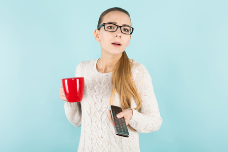 Portrait of attractive young woman in eyeglasses and sweater isolated on blue background holding TV remote and red mug changing channels being bored concept.