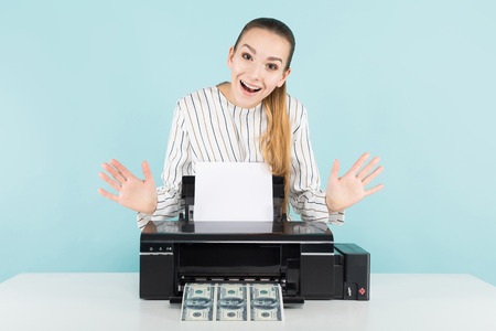 Portrait of attractive happy woman in striped shirt isolated on blue background printing dollar banknotes counterfeiter greed concept.