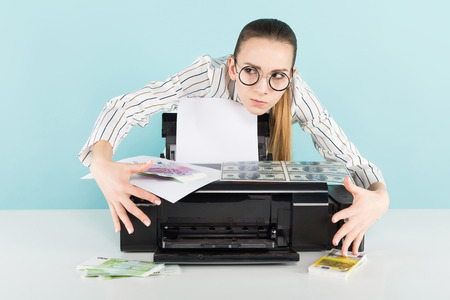 Portrait of attractive happy woman in striped shirt and eyeglasses isolated on blue background printing dollar and euro banknotes counterfeiter greed concept.