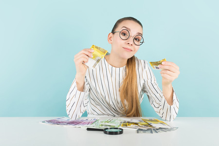 Portrait of attractive woman in striped shirt and eyeglasses isolated on blue background with magnifying glass counting euro banknotes checking if it is fake counterfeiter concept.