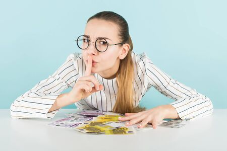 Attractive woman in striped shirt and eyeglasses isolated on blue background holding euro banknotes and showing keep silence gesture with her finger near mouth counterfeiter greed secrets concept.