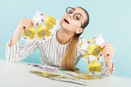 Portrait of attractive happy woman in striped shirt and eyeglasses isolated on blue background holding fans of euro banknotes counterfeiter greed or winning in lottery concept.