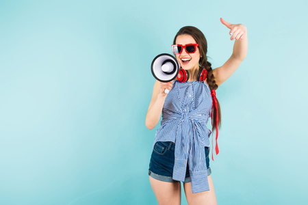 Brunette cheerful young woman DJ with in striped shirt and sunglasses on blue background with copyspace holding red headphones on her neck and speaking into megaphone making announcement concept. Stock Photo