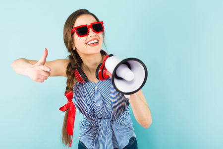 Brunette cheerful young woman DJ with in striped shirt and sunglasses on blue background holding red headphones on her neck and speaking into megaphone with thumb up making announcement concept. Stock Photo