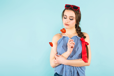 Portrait of attractive young pin-up woman in striped shirt with isolated on blue background with copyspace holding two heart-shaped candies on sticks.