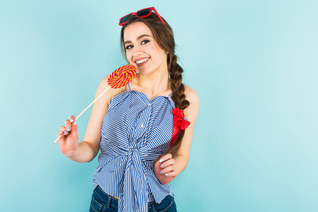 Portrait of brunette young pin-up woman in striped shirt and jeans with sunglasses isolated on blue background with copyspace holding multicolored candy on stick and touching hair. Stock Photo