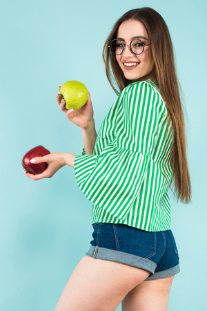 Portrait of attractive young long-haired girl in striped shirt, glasses and jeans shorts holding red and green apples isolated on blue background with copyspace healthy way of life concept.