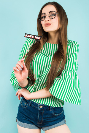 Portrait of attractive brunette young woman with in green striped shirt, glasses and jeans shorts on blue background holding kiss me sign fashion and beauty advertisement concept.