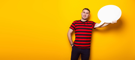 Portrait of handsome businessman in striped red T-shirt holds blank paper thinking speech bubble with empty space for your text isolated on orange background thinks of solution concept horizontal.