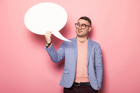 Portrait of handsome businessman in pink jumper, blue jacket and glasses holds blank paper thinking speech bubble with empty space for your text isolated on pink background open minded man concept. Stock Photo