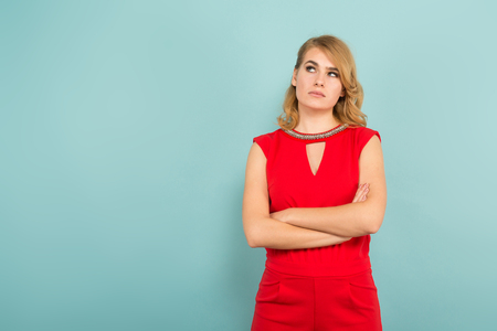 Portrait of thoughtful attractive blonde woman in red costume holding her hands crossed isolated on blue background with copyspace sales discount difficult choice concept. Stock Photo