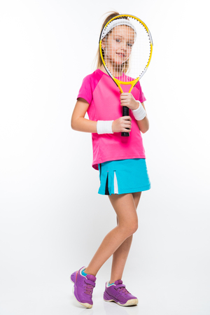 Adorable smiling little girl in sportswear holding tennis racket with her hands on white background brunette caucasian beautiful funny attractive friendly isolated