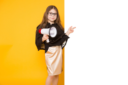 Portrait of cute long-haired little girl in jacket and eyeglassesisolated on yellow background pointing at emty blank board and holding megaphone your text here concept.