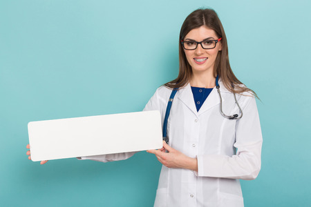 Female doctor in white coat and glasses with braces on teeth presents blank white rectangle board isolated on blue background with copyspace advertising concept.