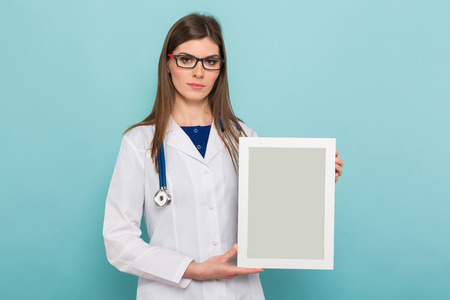 Portrait of female brunette doctor in white coat and eyeglasses holds blank white frame isolated on blue background with copyspace medical award concept.