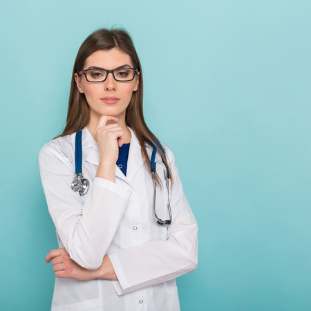 Portrait of female brunette doctor in white coat and eyeglasses with stethoscope propping up her chin isolated on blue background with copyspace head physician concept.