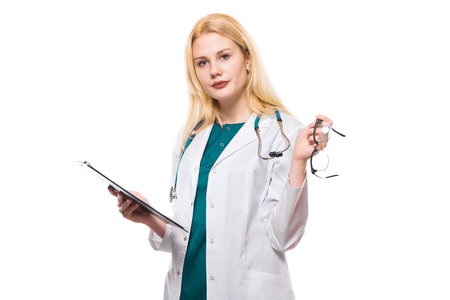 Portrait of female doctor in white coat wearing stethoscope reading some medical record application form clipped to pad and holding eyeglasses in hand isolated on white background with copyspace.
