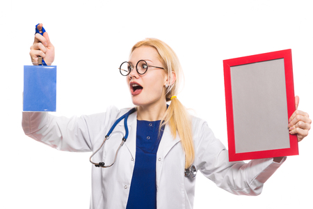 Shocked female doctor in white coat with stethoscope and glasses holds blank badge ID card or pass and frame isolated on white background celebrating medical conference award or diploma concept. Stock Photo