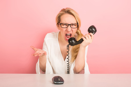Annoyed dissatisfied furious businesswoman isolated on pink background shout at vintage phone and working with mouse on computer displeased client complain about bad service, argue on phone concept. Stock Photo