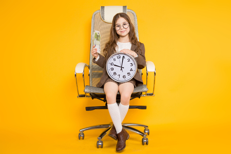 Long-haired little girl in eyeglasses sits in chair wearing brown jacket, shorts and white knee-socks with watches and fan of euro bills isolated on orange background with copyspace time is money. 写真素材