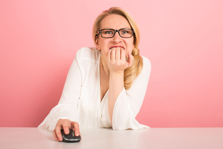 Attractive businesswoman in glasses working on computer with mouse bite her nails see something thrilling on screen isolated on pink background female manager working on the internet concept. Imagens