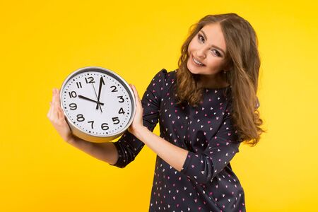 Portrait of attractive smiling brunette woman holding clocks isolated on yellow backgroung punctuality or being late concept.