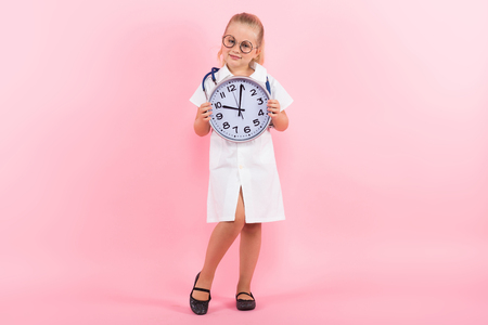 Portrait of little girl dressed like doctor in white coat and eyeglasses wearing stethoscope and holding clocks isolated on pink background with copyspace pediatrics time to take medicine concept.