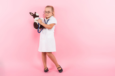 Portrait of little girl dressed like doctor in white coat and eyeglasses listening stethoscope to a plush rabbit isolated on pink background with copyspace pediatrics concept.