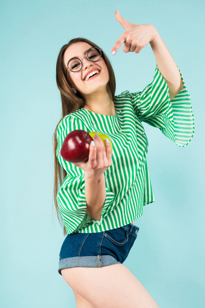 Portrait of attractive young long-haired girl in striped shirt, glasses and jeans shorts pointing at red and green apples isolated on blue background with copyspace healthy way of life concept.